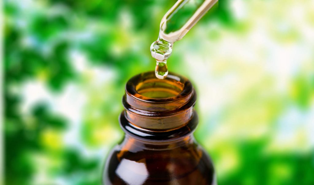 Glass dropper filled with herbal essence, aromatherapy oil, homeopathic medicine, or other liquid.